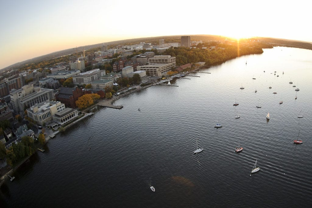 Boats dot Lake Mendota in an aerial view of the UW-Madison campus at sunset.