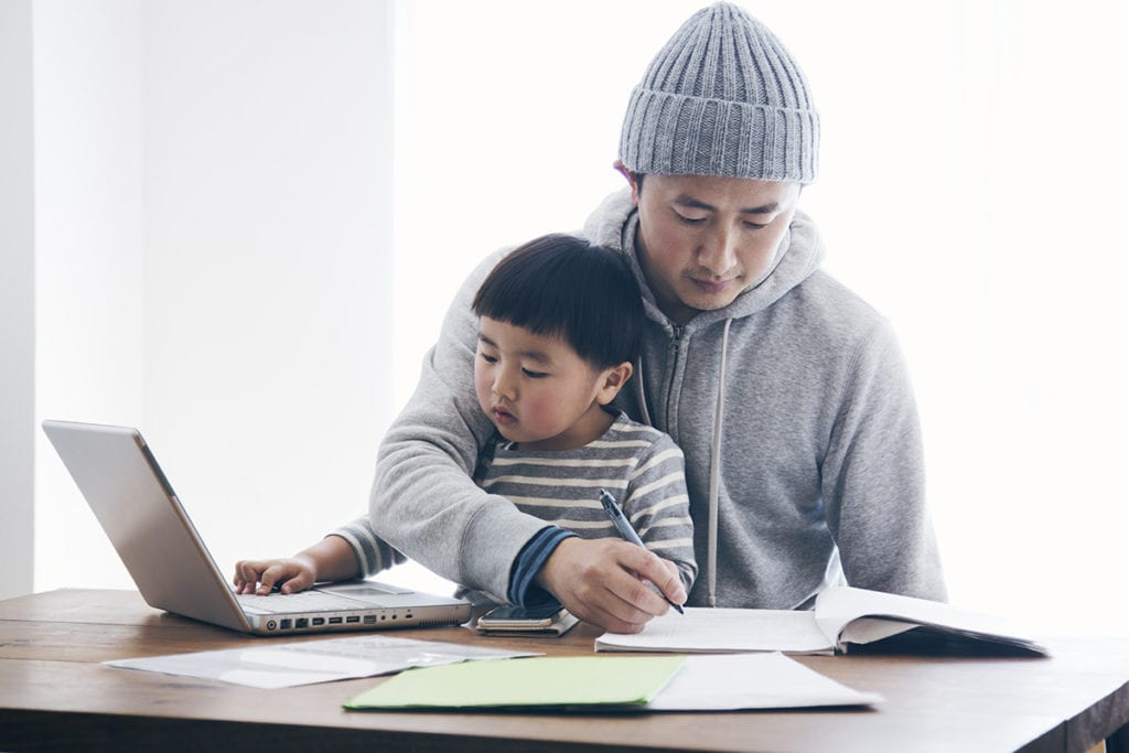 A dad and toddler son work on homework together.