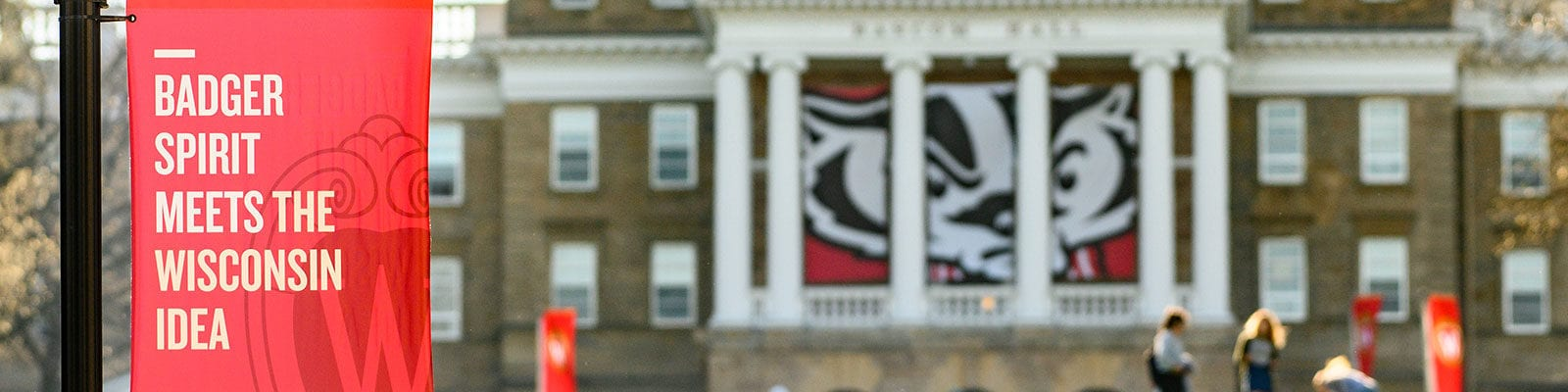 "Bascom Hall, a flag flies in front that says ""Badger spirit meets the Wisconsin Idea"""