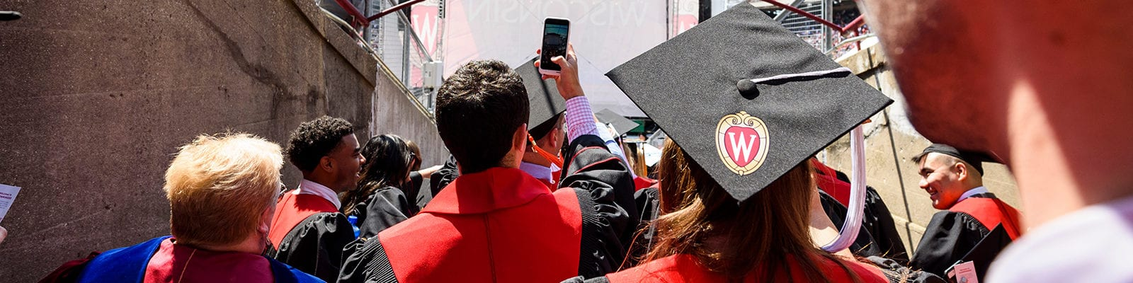 a UW-Madison graduate takes a photo on graduation day