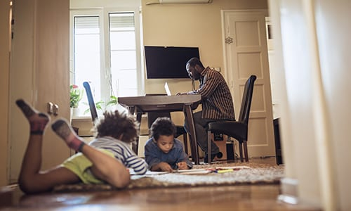 a man studies at the kitchen table while his kids play nearby