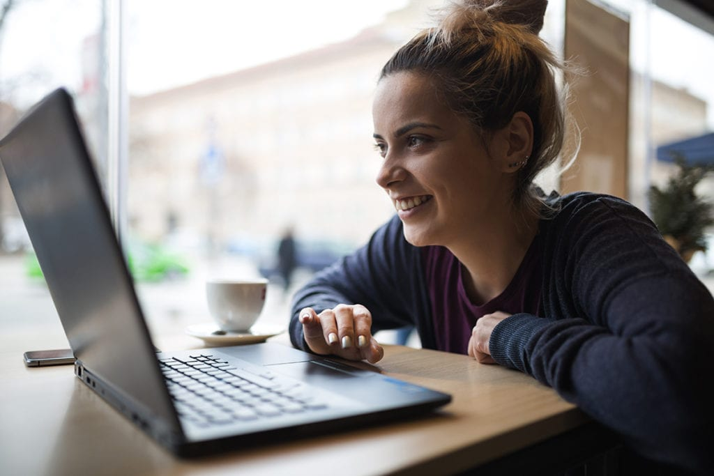 A smiling young woman studies at a coffee shop.