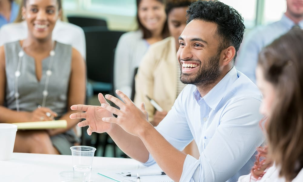Young male business student poses humorous question during lecture.