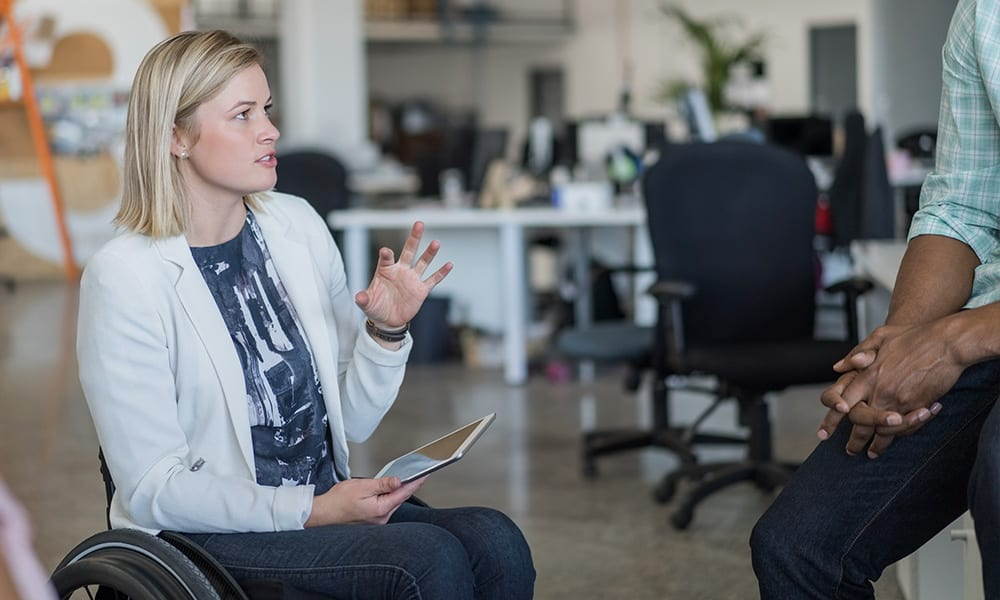 Photo of two co-workers talking in an office.