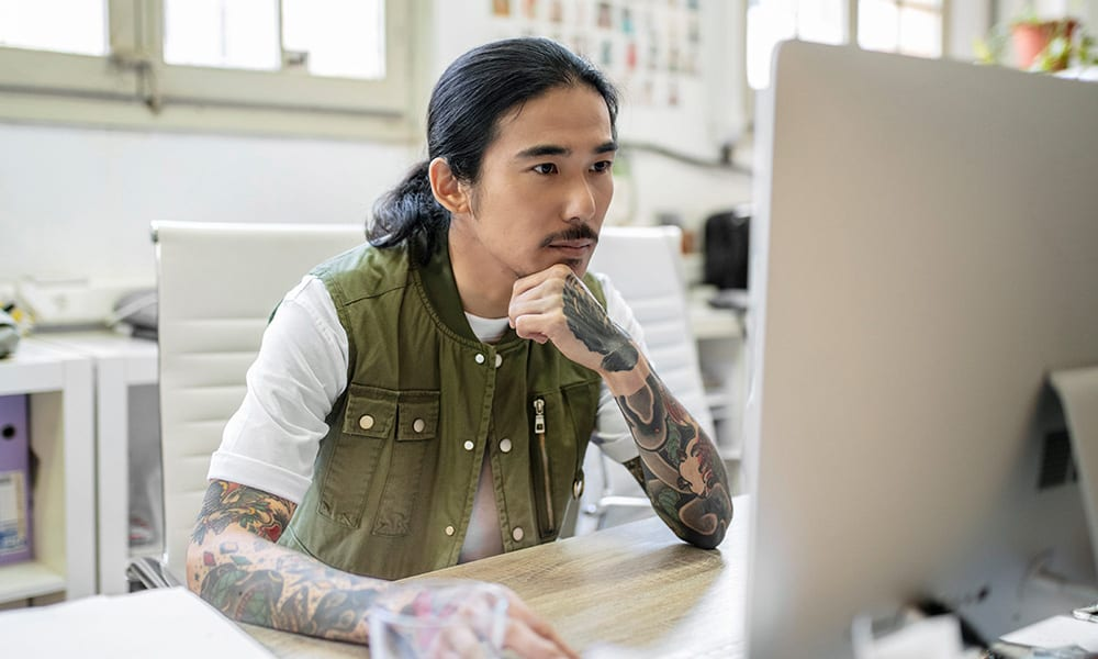 A tattooed student works on a computer.